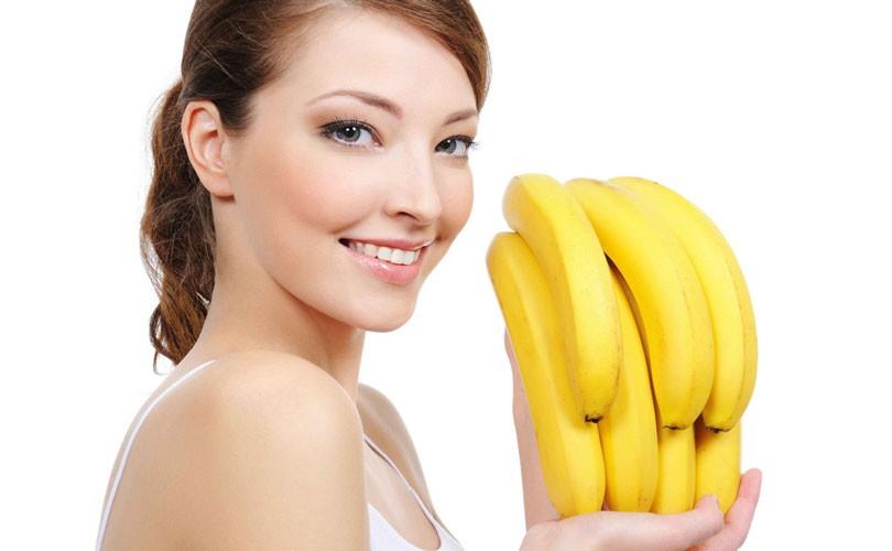 девушка держит в руках банан.